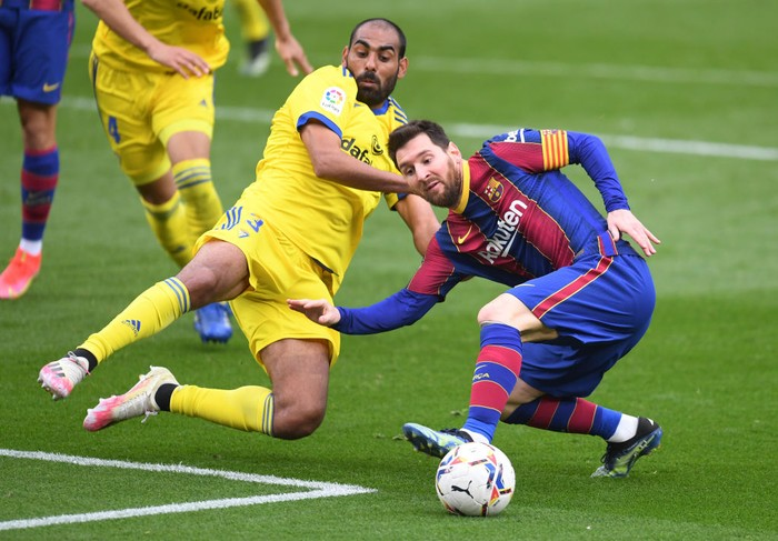 BARCELONA, SPAIN - FEBRUARY 21: Lionel Messi of FC Barcelona is challenged by Fali of Cadiz CF during the La Liga Santander match between FC Barcelona and Cadiz CF at Camp Nou on February 21, 2021 in Barcelona, Spain. Sporting stadiums around Spain remain under strict restrictions due to the Coronavirus Pandemic as Government social distancing laws prohibit fans inside venues resulting in games being played behind closed doors. (Photo by Alex Caparros/Getty Images)