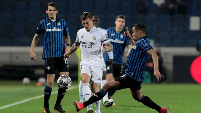 BERGAMO, ITALY - FEBRUARY 24: Toni Kroos of Real Madrid is tackled by Luis Muriel of Atalanta B.C. during the UEFA Champions League Round of 16 match between Atalanta and Real Madrid at Gewiss Stadium on February 24, 2021 in Bergamo, Italy. Sporting stadiums around Italy remain under strict restrictions due to the Coronavirus Pandemic as Government social distancing laws prohibit fans inside venues resulting in games being played behind closed doors. (Photo by Emilio Andreoli/Getty Images)