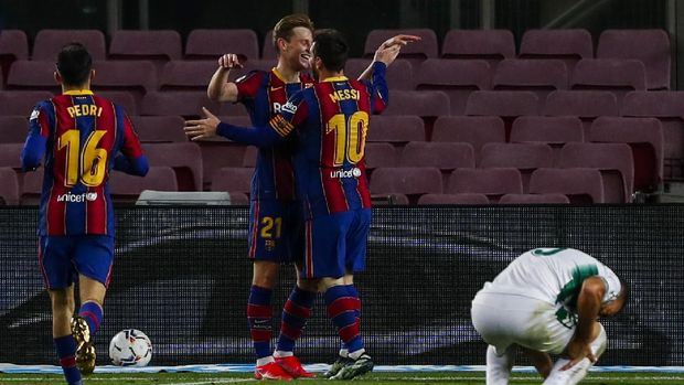 Barcelona's Lionel Messi, second right, is congratulated by Barcelona's Frenkie de Jong after scoring the second goal during the Spanish La Liga soccer match between FC Barcelona and Elche at the Camp Nou stadium in Barcelona, Spain, Wednesday, Feb. 24, 2021. (AP Photo/Joan Monfort)