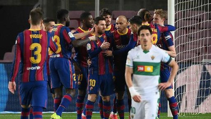 Barcelonas Argentinian forward Lionel Messi (C) celebrates with teammates after scoring a goal during the Spanish league football match between FC Barcelona and Elche CF at the Camp Nou stadium in Barcelona on February 24, 2021. (Photo by LLUIS GENE / AFP)