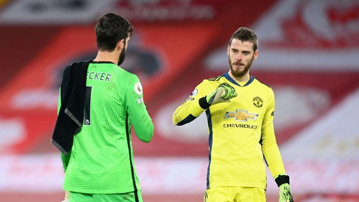 LIVERPOOL, ENGLAND - JANUARY 17: Alisson Becker of Liverpool interacts with David De Gea of Manchester United after the Premier League match between Liverpool and Manchester United at Anfield on January 17, 2021 in Liverpool, England. Sporting stadiums around England remain under strict restrictions due to the Coronavirus Pandemic as Government social distancing laws prohibit fans inside venues resulting in games being played behind closed doors. (Photo by Michael Regan/Getty Images)