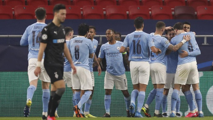 Manchester City players celebrate after Bernardo Silva scored his sides opening goal during the Champions League round of 16 first leg soccer match between Borussia Monchengladbach and Manchester City at the Puskas Arena stadium in Budapest, Hungary, Wednesday, Feb. 24, 2021. (AP Photo/Laszlo Balogh)