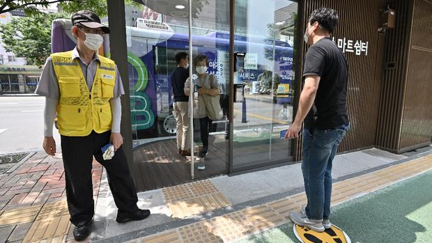 A man (R) checks his temperature in front of a thermal imaging camera to enter a shelter booth designed to protect passengers from monsoon rains, summer heat and the COVID-19 coronavirus, at a bus stop in Seoul on August 12, 2020. - Automatic temperature checks before entry, sliding doors and an air-conditioning system equipped with ultraviolet disinfection lamps -- welcome to high-tech South Korea's latest front in the battle against coronavirus: the bus shelter. (Photo by Jung Yeon-je / AFP)