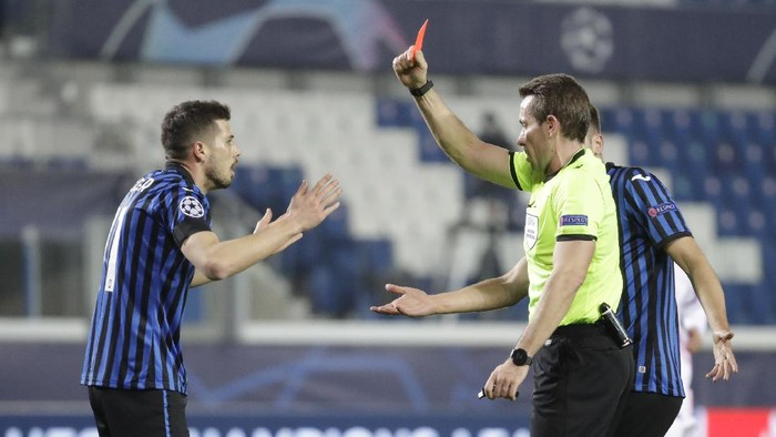 Referee Tobias Stieler, right, shows a red card to Atalantas Remo Freuler during the Champions League, round of 16, first leg soccer match between Atalanta and Real Madrid, at the Gewiss Stadium in Bergamo, Wednesday, Feb. 24, 2021. (AP Photo/Luca Bruno)