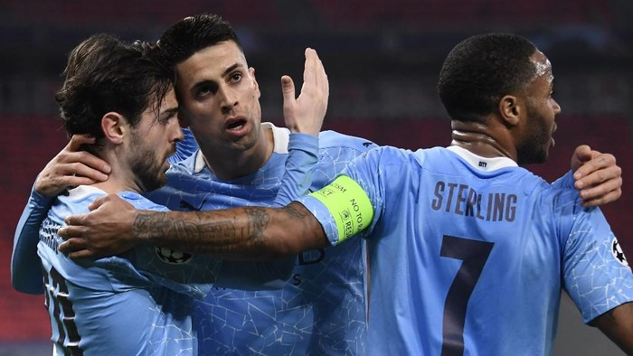 Manchester Citys Portuguese midfielder Bernardo Silva (L) celebrates with Manchester Citys Portuguese defender Joao Cancelo (C) and Manchester Citys English midfielder Raheem Sterling scoring his teams first goal during the UEFA Champions League, last 16, 1st-leg football match Borussia Moenchengladbach v Manchester City at the Puskas Arena in Budapest on February 24, 2021. (Photo by Attila KISBENEDEK / AFP)
