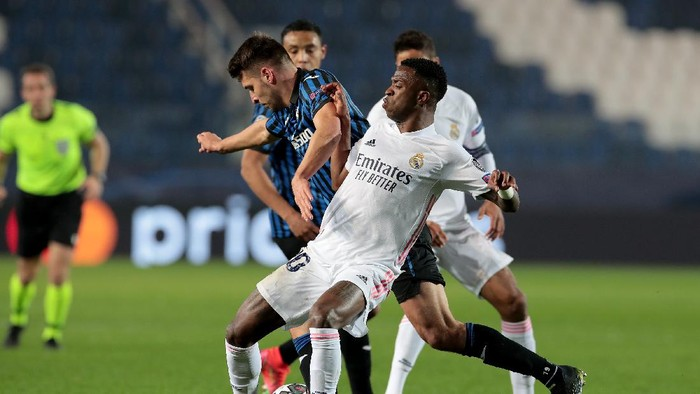 BERGAMO, ITALY - FEBRUARY 24: Vinicius Junior of Real Madrid battles for possession with Berat Djimsiti of Atalanta B.C. during the UEFA Champions League Round of 16 match between Atalanta and Real Madrid at Gewiss Stadium on February 24, 2021 in Bergamo, Italy. Sporting stadiums around Italy remain under strict restrictions due to the Coronavirus Pandemic as Government social distancing laws prohibit fans inside venues resulting in games being played behind closed doors. (Photo by Emilio Andreoli/Getty Images)