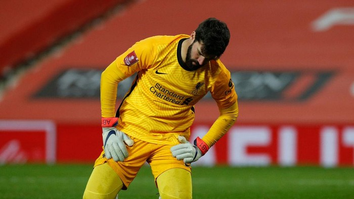 MANCHESTER, ENGLAND - JANUARY 24: Alisson Becker of Liverpool reacts as Marcus Rashford of Manchester United (not pictured) scores their sides second goal  during The Emirates FA Cup Fourth Round match between Manchester United and Liverpool at Old Trafford on January 24, 2021 in Manchester, England. Sporting stadiums around the UK remain under strict restrictions due to the Coronavirus Pandemic as Government social distancing laws prohibit fans inside venues resulting in games being played behind closed doors. (Photo by Phil Noble - Pool/Getty Images)