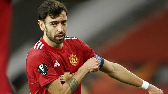 Manchester Uniteds Bruno Fernandes adjusts his captain armband during the Europa League round of 32, second leg, soccer match between Manchester United and Real Sociedad at Old Trafford in Manchester, England, Thursday, Feb. 25, 2021. (AP Photo/Dave Thompson)