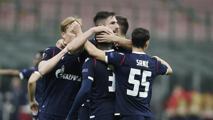 Red Stars El Fardou Ben, covered by his teammates celebrates after scoring his sides opening goal during the Europa League round of 32 second leg soccer match between AC Milan and Red Star Belgrade at the San Siro Stadium, in Milan, Italy, Thursday, Feb. 25, 2021. (AP Photo/Antonio Calanni)