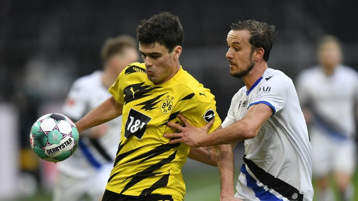 Dortmunds Giovanni Reyna, left, challenges for the ball with Arminias Manuel Prietl during the German Bundesliga soccer match between Borussia Dortmund and Arminia Bielefeld in Dortmund, Germany, Saturday, Feb. 27, 2021. (AP Photo/Martin Meissner, Pool)