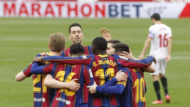 Barcelona's Ousmane Dembele, center back to camera, celebrates with teammates after scoring during a Spanish La Liga soccer match between Sevilla and Barcelona at the Ramon Sanchez-Pizjuan stadium in Seville, Spain, Saturday Feb. 27, 2021. (AP Photo/Angel Fernandez)