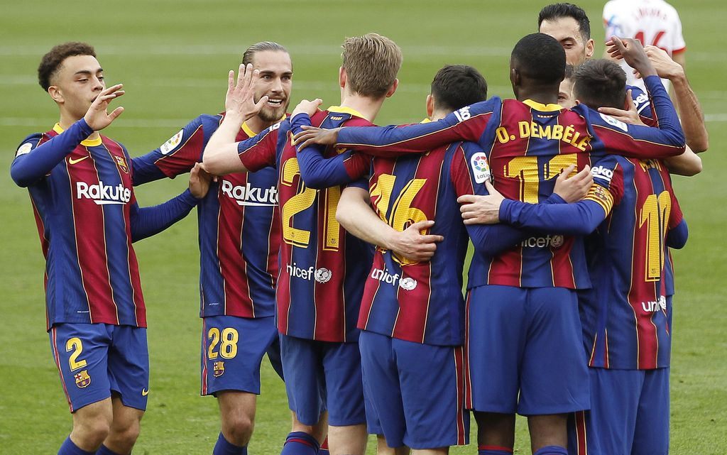 Barcelona's Ousmane Dembele, third right, celebrates with teammates after scoring during a Spanish La Liga soccer match between Sevilla and Barcelona at the Ramon Sanchez-Pizjuan stadium in Seville, Spain, Saturday Feb. 27, 2021. (AP Photo/Angel Fernandez)