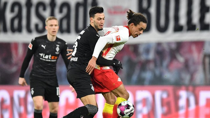 LEIPZIG, GERMANY - FEBRUARY 27: Yussuf Poulsen of RB Leipzig is challenged by Ramy Bensebaini of Borussia Moenchengladbach during the Bundesliga match between RB Leipzig and Borussia Moenchengladbach at Red Bull Arena on February 27, 2021 in Leipzig, Germany. Sporting stadiums around Germany remain under strict restrictions due to the Coronavirus Pandemic as Government social distancing laws prohibit fans inside venues resulting in games being played behind closed doors. (Photo by Stuart Franklin/Getty Images)