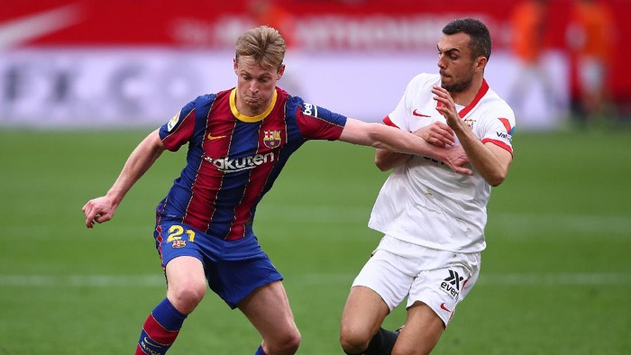 SEVILLE, SPAIN - FEBRUARY 27: Frenkie de Jong of FC Barcelona holds off Joan Jordan of Sevilla during the La Liga Santander match between Sevilla FC and FC Barcelona at Estadio Ramon Sanchez Pizjuan on February 27, 2021 in Seville, Spain. Sporting stadiums around Spain remain under strict restrictions due to the Coronavirus Pandemic as Government social distancing laws prohibit fans inside venues resulting in games being played behind closed doors. (Photo by Fran Santiago/Getty Images)