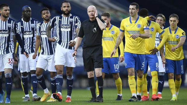 Referee Lee Mason, cen tre,confers with the video assistant referee during the English Premier League soccer match between West Bromwich Albion and Brighton and Hove Albion at the Hawthorns, West Bromwich, England, Saturday, Feb. 27, 2021. (Peter Powell/Pool via AP)
