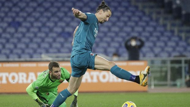 AC Milan's Zlatan Ibrahimovic, right attempts to score a goal with a back heel shot but Roma's goalkeeper Pau Lopez saves during the Serie A soccer match between AS Roma and AC Milan at the Olympic stadium, in Rome, Italy, Sunday, Feb. 28, 2021.(AP Photo/Gregorio Borgia)