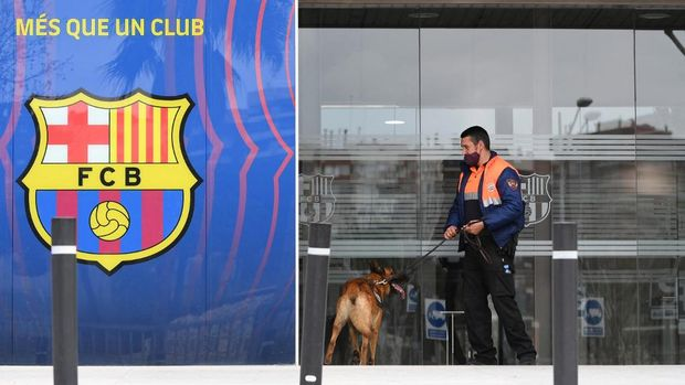 A security guard enters the offices of Barcelona Football Club with a dog on March 01, 2021 in Barcelona during a police operation inside the building. - Police raided the offices of FC Barcelona on March 01, 2021, carrying out several arrests just six days ahead of the club's presidential elections, a Catalan regional police spokesman told AFP. Spain's Cadena Ser radio said one of those arrested was former club president Josep Maria Bartomeu, who resigned in October, along with CEO Oscar Grau and the club's head of legal services. (Photo by LLUIS GENE / AFP)