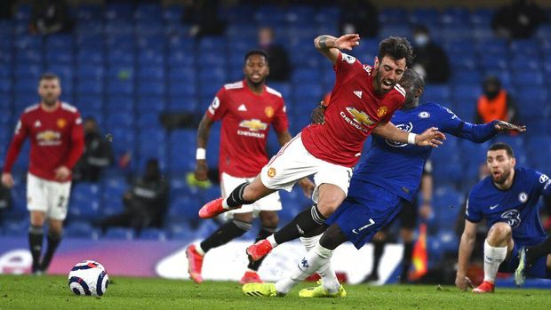 Manchester United's Bruno Fernandes, centre, and Chelsea's N'Golo Kante challenge for the ball during the English Premier League soccer match between Chelsea and Manchester United at Stamford Bridge Stadium in London, England, Sunday, Feb. 28, 2021. (Andy Rain/Pool via AP)