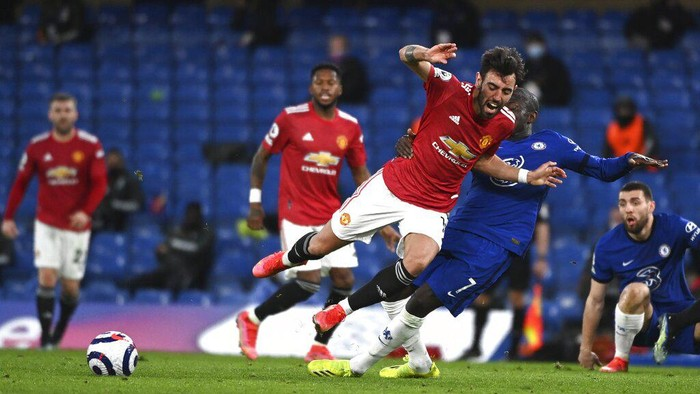 Manchester Uniteds Bruno Fernandes, centre, and Chelseas NGolo Kante challenge for the ball during the English Premier League soccer match between Chelsea and Manchester United at Stamford Bridge Stadium in London, England, Sunday, Feb. 28, 2021. (Andy Rain/Pool via AP)