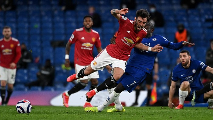 LONDON, ENGLAND - FEBRUARY 28: Bruno Fernandes of Manchester United is tackled by NGolo Kante of Chelsea  during the Premier League match between Chelsea and Manchester United at Stamford Bridge on February 28, 2021 in London, England. Sporting stadiums around the UK remain under strict restrictions due to the Coronavirus Pandemic as Government social distancing laws prohibit fans inside venues resulting in games being played behind closed doors. (Photo by Andy Rain - Pool/Getty Images)