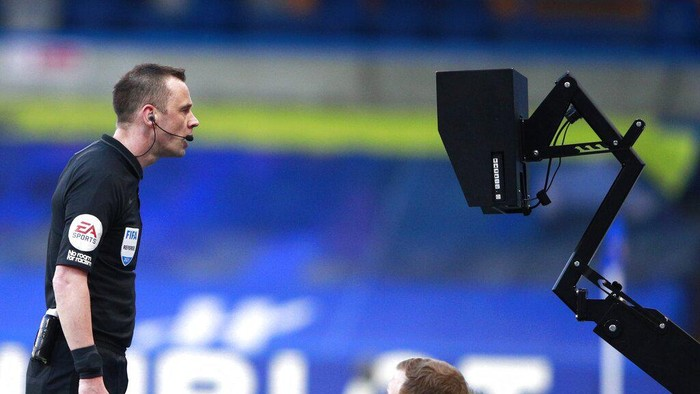 Referee Stuart Attwell watching the VAR monitor during the English Premier League soccer match between Chelsea and Manchester United at Stamford Bridge Stadium in London, England, Sunday, Feb. 28, 2021. (AP Photo/Ian Walton, Pool)
