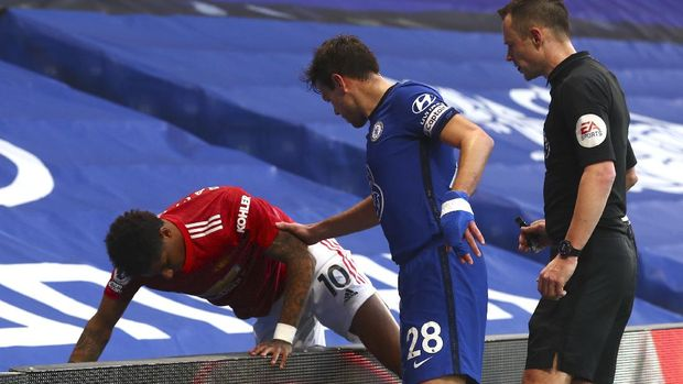 Manchester United's Marcus Rashford, left, is helped by Chelsea's Cesar Azpilicueta, centre, after colliding with an advertising board during the English Premier League soccer match between Chelsea and Manchester United at Stamford Bridge Stadium in London, England, Sunday, Feb. 28, 2021. (Clive Rose/Pool via AP)