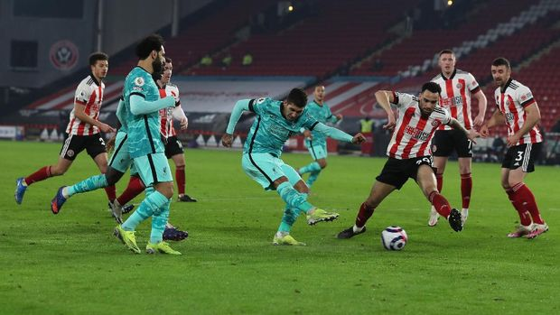 SHEFFIELD, ENGLAND - FEBRUARY 28: Roberto Firminho of Liverpool scores their side's second goal whilst under pressure from Kean Bryan of Sheffield United during the Premier League match between Sheffield United and Liverpool at Bramall Lane on February 28, 2021 in Sheffield, England. Sporting stadiums around the UK remain under strict restrictions due to the Coronavirus Pandemic as Government social distancing laws prohibit fans inside venues resulting in games being played behind closed doors. (Photo by Lee Smith - Pool/Getty Images)