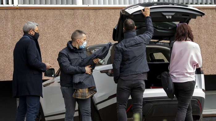 Journalists work outside FC Barcelona's offices in Barcelona, Spain, Monday March 1, 2021. Spanish police detained several people after raiding Barcelona's stadium in a search and seize operation related to an investigation into club officials. Police say detentions were made but do not say who or how many people were taken into custody.  (AP Photo/Joan Monfort)