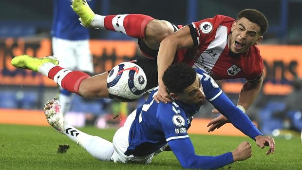Southampton's Che Adams, top, and Everton's Ben Godfrey challenge for the ball during the English Premier League soccer match between Everton and Southampton at Goodison Park in Liverpool, England, Monday, March 1, 2021. (Gareth Copley/Pool via AP)
