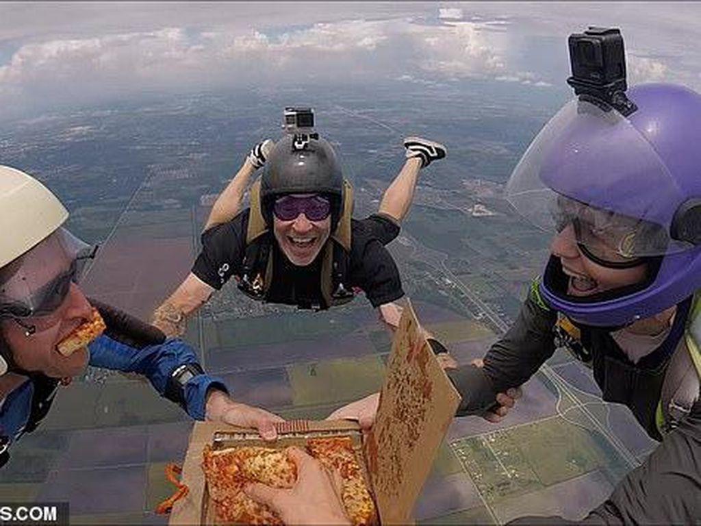 Gokil! Wanita Ini Asyik Makan Pizza Sambil Terjun Payung di Udara