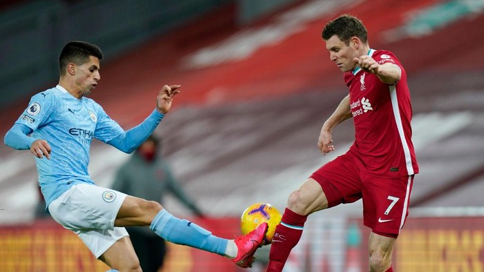 LIVERPOOL, ENGLAND - FEBRUARY 07: Joao Cancelo of Manchester City battles for possession with James Milner of Liverpool during the Premier League match between Liverpool and Manchester City at Anfield on February 07, 2021 in Liverpool, England. Sporting stadiums around the UK remain under strict restrictions due to the Coronavirus Pandemic as Government social distancing laws prohibit fans inside venues resulting in games being played behind closed doors (Photo by Tim Keeton - Pool/Getty Images)