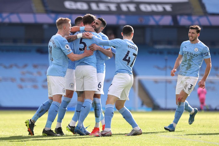 MANCHESTER, ENGLAND - FEBRUARY 27: John Stones of Manchester City celebrates with teammates Oleksandr Zinchenko, Riyad Mahrez, Phil Foden and Ruben Dias after scoring his team's second goal during the Premier League match between Manchester City and West Ham United at Etihad Stadium on February 27, 2021 in Manchester, England. Sporting stadiums around the UK remain under strict restrictions due to the Coronavirus Pandemic as Government social distancing laws prohibit fans inside venues resulting in games being played behind closed doors. (Photo by Clive Brunskill/Getty Images)