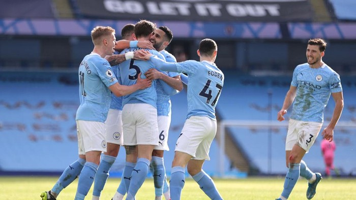 MANCHESTER, ENGLAND - FEBRUARY 27: John Stones of Manchester City celebrates with teammates Oleksandr Zinchenko, Riyad Mahrez, Phil Foden and Ruben Dias after scoring his teams second goal during the Premier League match between Manchester City and West Ham United at Etihad Stadium on February 27, 2021 in Manchester, England. Sporting stadiums around the UK remain under strict restrictions due to the Coronavirus Pandemic as Government social distancing laws prohibit fans inside venues resulting in games being played behind closed doors. (Photo by Clive Brunskill/Getty Images)