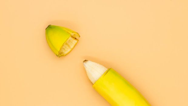 Banana with the tip of the peel cut off, the concept of male circumcision
