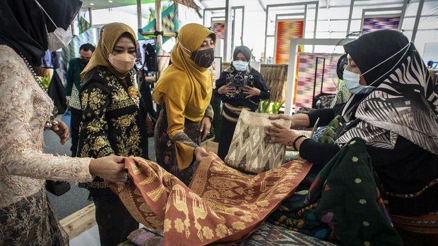 Pelaku UMKM melayani calon pembeli dalam acara Karya Kreatif Indonesia (KKI) 2021 Eksotisme Lombok di kawasan destinasi pariwisata super prioritas (DPSP) The Mandalika, Praya, Lombok Tengah, NTB, Rabu (3/3/2021). KKI 2021 Eksotisme Lombok dengan tema Sinergi, Globalisasi, dan Digitalisasi UMKM dan Sektor Pariwisata itu bertujuan untuk mendukung Gerakan Nasional Bangga Buatan Indonesia dan Bangga Berwisata #DiIndonesiaAja. ANTARA FOTO/Aprillio Akbar/hp.