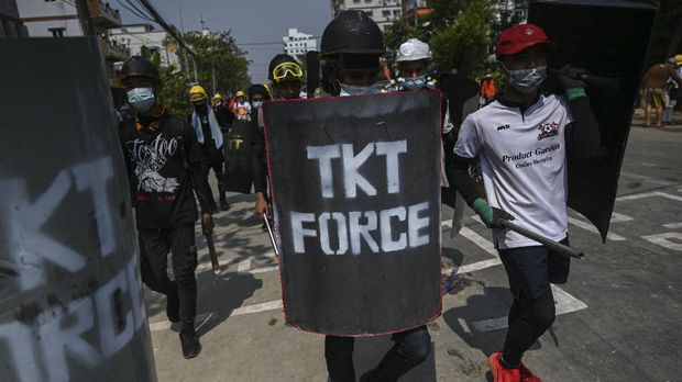 Protesters walk with homemade shields during a demonstration against the military coup in Yangon on March 3, 2021. (Photo by STR / AFP)