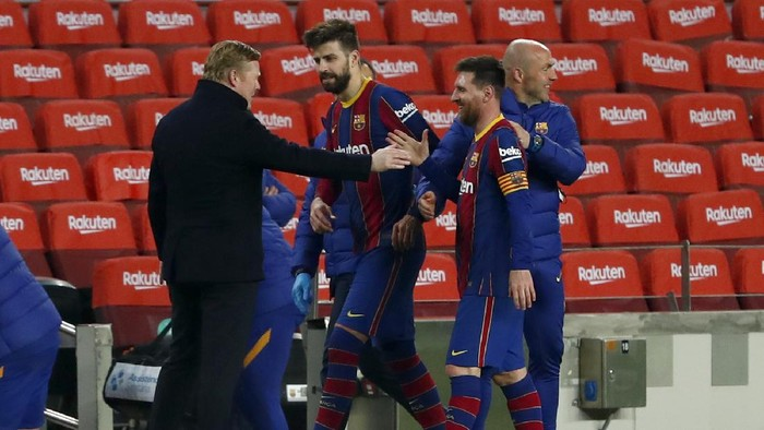 Barcelonas Lionel Messi shakes hands with Barcelonas head coach Ronald Koeman at the end of the the Copa del Rey semifinal, second leg, soccer match between FC Barcelona and Sevilla FC at the Camp Nou stadium in Barcelona, Spain, Wednesday March 3, 2021. Barcelona won 3-0. (AP Photo/Joan Monfort)