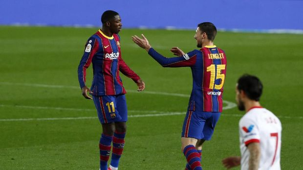 Barcelona's Ousmane Dembele, left, celebrates after scoring the opening goal during the the Copa del Rey semifinal, second leg, soccer match between FC Barcelona and Sevilla FC at the Camp Nou stadium in Barcelona, Spain, Wednesday March 3, 2021. (AP Photo/Joan Monfort)