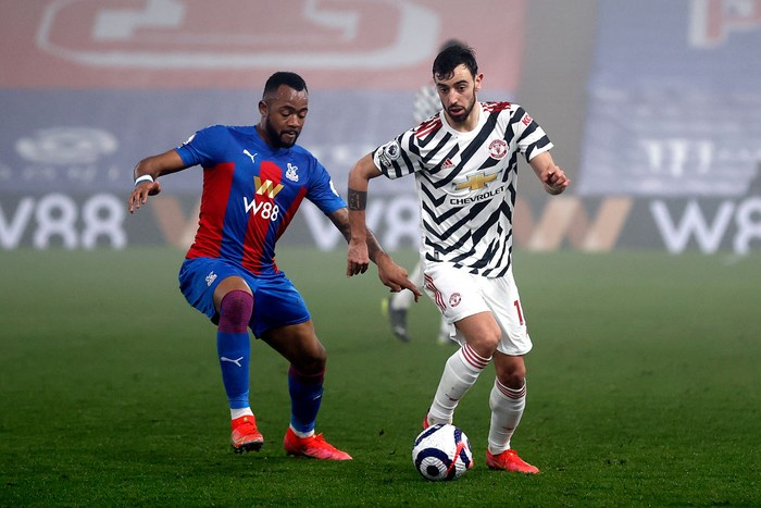 LONDON, ENGLAND - MARCH 03: Bruno Fernandes of Manchester United battles for possession with Jordan Ayew of Crystal Palace during the Premier League match between Crystal Palace and Manchester United at Selhurst Park on March 03, 2021 in London, England. Sporting stadiums around the UK remain under strict restrictions due to the Coronavirus Pandemic as Government social distancing laws prohibit fans inside venues resulting in games being played behind closed doors. (Photo by Adrian Dennis - Pool/Getty Images)