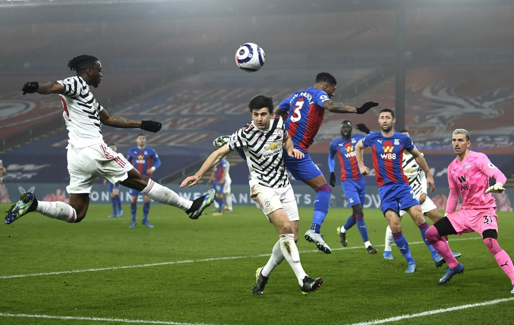 Manchester United's Aaron Wan-Bissaka, left, Harry Maguire and Crystal Palace's Patrick van Aanholt battle for the ball during the English Premier League soccer match between Crystal Palace and Manchester United at Selhurst Park stadium in London, England, Wednesday, March 3, 2021. (Mike Hewitt/Pool via AP)