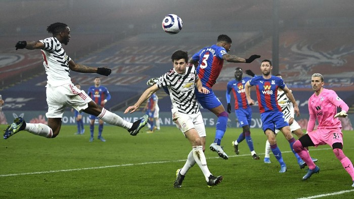 Manchester Uniteds Aaron Wan-Bissaka, left, Harry Maguire and Crystal Palaces Patrick van Aanholt battle for the ball during the English Premier League soccer match between Crystal Palace and Manchester United at Selhurst Park stadium in London, England, Wednesday, March 3, 2021. (Mike Hewitt/Pool via AP)