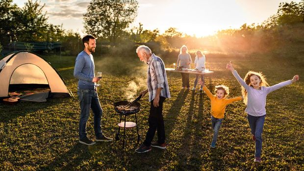 Happy multi-generation family enjoying while making barbecue during garden party at sunset. Kids are having fun.