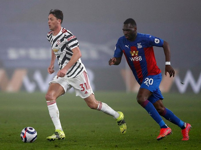 LONDON, ENGLAND - MARCH 03: Nemanja Matic of Manchester United runs with the ball whilst under pressure from Christian Benteke of Crystal Palace during the Premier League match between Crystal Palace and Manchester United at Selhurst Park on March 03, 2021 in London, England. Sporting stadiums around the UK remain under strict restrictions due to the Coronavirus Pandemic as Government social distancing laws prohibit fans inside venues resulting in games being played behind closed doors. (Photo by Adrian Dennis - Pool/Getty Images)
