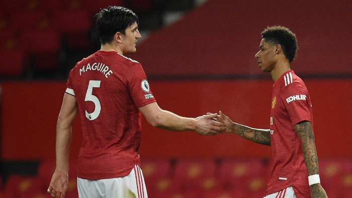 MANCHESTER, ENGLAND - FEBRUARY 21: Marcus Rashford of Manchester United celebrates with Harry Maguire after scoring his teams first goal during the Premier League match between Manchester United and Newcastle United at Old Trafford on February 21, 2021 in Manchester, England. Sporting stadiums around the UK remain under strict restrictions due to the Coronavirus Pandemic as Government social distancing laws prohibit fans inside venues resulting in games being played behind closed doors. (Photo by Oli Scarff - Pool/Getty Images)