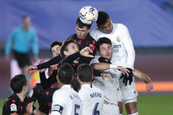Real Madrid and Real Sociedad players jump for the header during the Spanish La Liga soccer match between Real Madrid and Real Sociedad at Alfredo di Stefano stadium in Madrid, Spain, Monday, March 1, 2021. (AP Photo/Bernat Armangue)