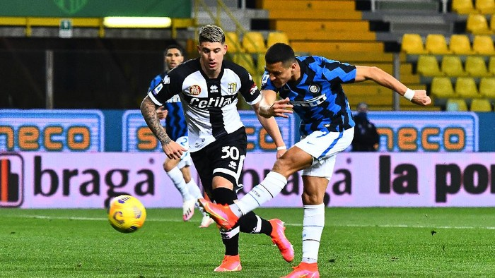 PARMA, ITALY - MARCH 04: Alexis Sanchez of Internazionale scores his sides first goal whilst under pressure from Lautaro Valenti of Parma Calcio 1913 during the Serie A match between Parma Calcio and FC Internazionale at Stadio Ennio Tardini on March 04, 2021 in Parma, Italy. Sporting stadiums around Italy remain under strict restrictions due to the Coronavirus Pandemic as Government social distancing laws prohibit fans inside venues resulting in games being played behind closed doors. (Photo by Alessandro Sabattini/Getty Images)