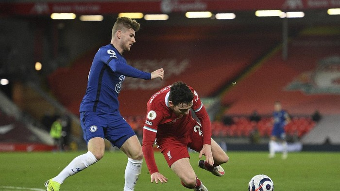 Chelseas Timo Werner, left, challenges for the ball with Liverpools Andrew Robertson during the English Premier League soccer match between Liverpool and Chelsea at Anfield stadium in Liverpool, England, Thursday, March 4, 2021. (Oli Scarff, Pool via AP)