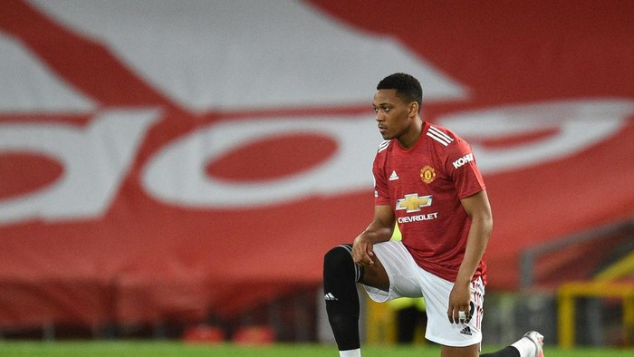 MANCHESTER, ENGLAND - FEBRUARY 21: Anthony Martial of Manchester United takes a knee in support of the Black Lives Matter movement prior to the Premier League match between Manchester United and Newcastle United at Old Trafford on February 21, 2021 in Manchester, England. Sporting stadiums around the UK remain under strict restrictions due to the Coronavirus Pandemic as Government social distancing laws prohibit fans inside venues resulting in games being played behind closed doors. (Photo by Oli Scarff - Pool/Getty Images)