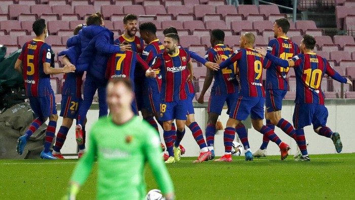 Barcelonas Gerard Pique, background center left, celebrates after scoring his sides second goal during the the Copa del Rey semifinal, second leg, soccer match between FC Barcelona and Sevilla FC at the Camp Nou stadium in Barcelona, Spain, Wednesday March 3, 2021. (AP Photo/Joan Monfort)