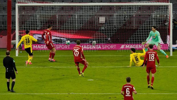 MUNICH, GERMANY - MARCH 06: Robert Lewandowski of FC Bayern Muenchen  scores their team's first goal  during the Bundesliga match between FC Bayern Muenchen and Borussia Dortmund at Allianz Arena on March 06, 2021 in Munich, Germany. Sporting stadiums around Germany remain under strict restrictions due to the Coronavirus Pandemic as Government social distancing laws prohibit fans inside venues resulting in games being played behind closed doors. (Photo by Günter Schiffmann - Pool/Getty Images)